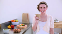Pretty model standing in kitchen drinking disposable cup of coffee Stock Footage