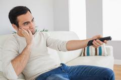 Handsome man getting bored of tv programs - stock photo