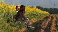 Happy family, young parent sitting on the field, baby coming to parents Stock Footage