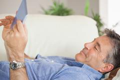 Smiling man laying on a sofa using a tablet pc - stock photo