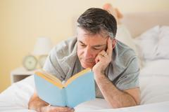 Concentrated man reading a book on his bed Stock Photos
