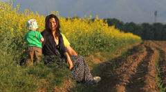 Cute baby and his young parents have fun together in nature, flourish rape field Stock Footage