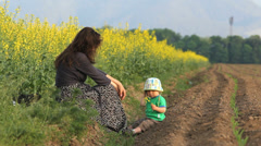 Great memories, cute baby and young baby spend time together in flourish field Stock Footage