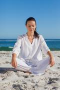 Stock Photo of Beautiful woman sitting on sand