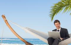 Businessman sitting in hammock using laptop looking at camera - stock photo