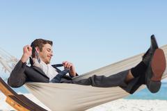 Smiling businessman lying in hamock taking off his tie Stock Photos