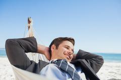 Businessman relaxing in hammock - stock photo