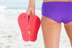 Rear view of a young woman holding flip flops Stock Photos