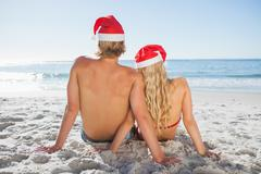 Rear view of couple sitting on beach - stock photo
