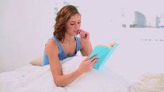 Pleased woman reading a book sitting in her bed Stock Footage