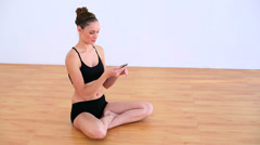 Pleased woman sitting on the floor using a mobile phone Stock Footage