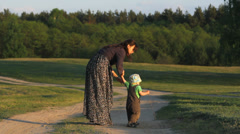 Mother and little baby on rustic path, lady try to convince boy to follow path Stock Footage