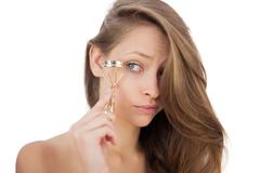 Puzzled brunette model looking an eyelash curler Stock Photos