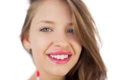 Stock Photo of Happy brunette girl holding a gloss tube