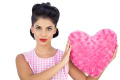 Unsmiling black hair model holding a pink heart shaped pillow - stock photo