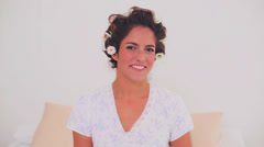 Happy woman in hair curlers applying gloss Stock Footage