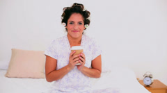 Cheerful woman in hair curlers enjoying coffee Stock Footage