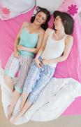 Friends in pajamas lying on bed and laughing Stock Photos