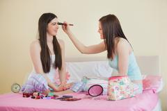 Smiling girl giving her friend a makeover at sleepover - stock photo