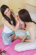 Happy girl giving her friend a makeover at sleepover - stock photo