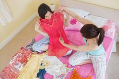 Cute girls looking at a dress at a sleepover - stock photo