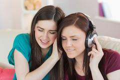 Stock Photo of Cheerful girl listening to music with her friend beside her on the sofa
