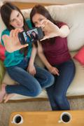 Two friends on the couch taking a selfie with smartphone Kuvituskuvat