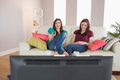Stock Photo of Two pretty friends on the couch watching tv together