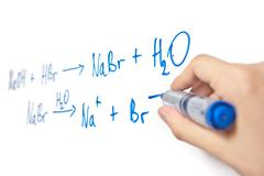 Chemical equation written on whiteboard with hand holding marker Stock Photos