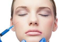 Peaceful pretty model having botox injection on the cheek Stock Photos