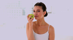 Amused beautiful woman smelling and showing an apple Stock Footage