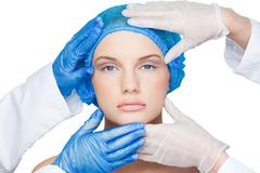 Stock Photo of Surgeons examining content blonde wearing blue surgical cap