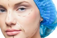Close up on pretty young patient with dotted lines on the face - stock photo