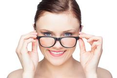 Smiling natural model looking over her classy glasses - stock photo