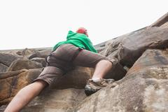 Determined man ascending a large rock face and seeing the top - stock photo