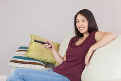 Happy asian girl watching tv smiling at camera Stock Photos