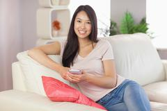 Pretty asian girl using her smartphone on the couch smiling at camera - stock photo