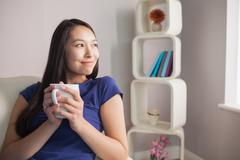 Stock Photo of Thinking young asian woman sitting on the couch holding mug