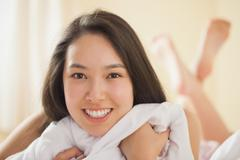 Stock Photo of Cute young asian woman grasping her duvet and smiling