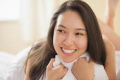 Cute young asian woman holding her duvet and smiling - stock photo