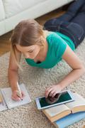 Focused young woman lying on floor using tablet to do her assignment - stock photo