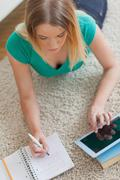 Woman lying on floor doing her homework using tablet - stock photo