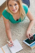 Happy woman lying on floor doing her homework using tablet - stock photo