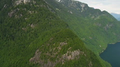 Aerial view freshwater lake forests of firs mountain peaks Rockies - stock footage