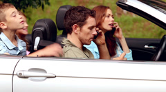 Parents on the phone in a convertible car Stock Footage