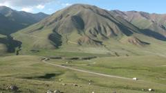 A car drives through spectacular mountain landscape in Kyrgyzstan Central Asia Stock Footage