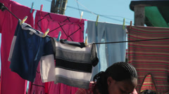 African woman hangs up washing in township,South Africa Stock Footage