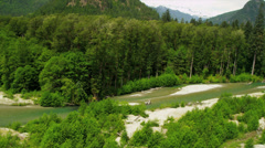 Aerial view river valley turquoise waters driftwood extreme terrain, Rockies - stock footage