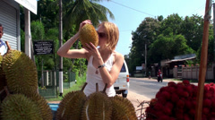 The girl on a street market with fruits of durian & rambutan. Sri Lanka. Stock Footage