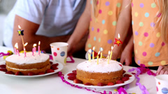 Family blowing out candles at a birthday party - stock footage